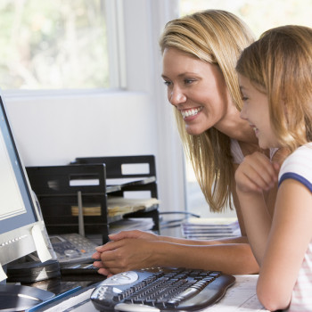 Woman And Young Girl In Home Office With Computer Smiling