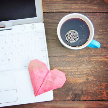 Laptop or notebook with cup of coffee and origami heart on old w